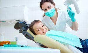The dentist checks the kid's oral health.